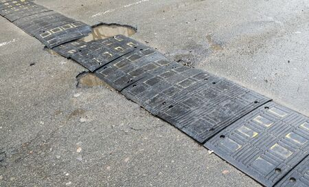 Damaged speed bump on the road after the rain.