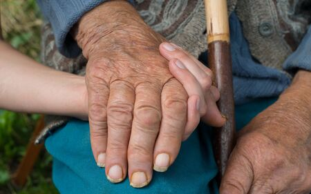Old and young woman holding hands together. Hands. Close-up.