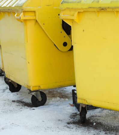 Yellow plastic waste containers (dustbins, garbage cans, trash cans) in winter.