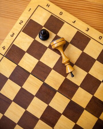 Pawn wins a victory over the king. Wooden chess pieces on the chessboard. Chess game. Top view.
