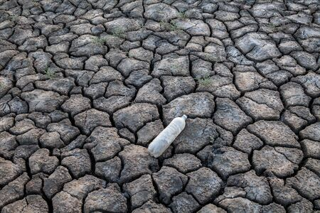 Old plastic bottle on the cracked dry ground