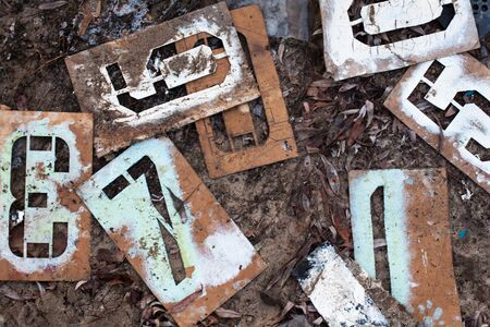 Old metal stencils with different figures on the ground.