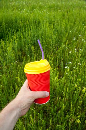 Hand holding bright red plastic cup with yellow lid and purple bendy drinking straw (tube) against the green grass background. Drinking coffee (tee) outdoors. Camping drink. Imagens