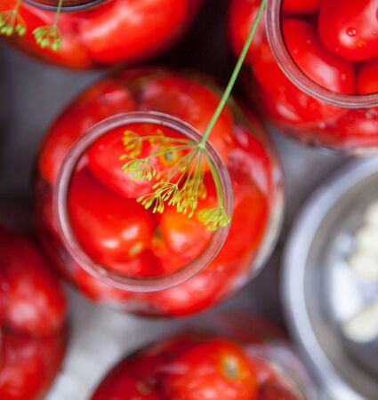 Pickling (canning) the tomatoes. Glass jars with tomatoes. Garlic in a metal plate.