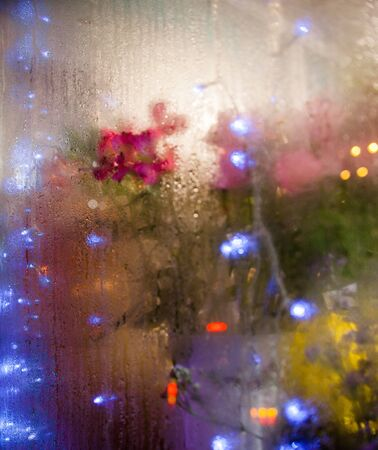 Flowers and light garlands behind the wet glass. Moist window. Water drops on the glass. Blurred lights. Wet transparent surface.
