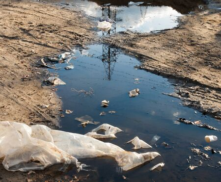 Garbage in the mud and puddles on the dirt road. Environmental pollution.
