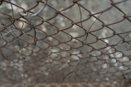 Chiuso il vecchio recinto di rete metallica di lerciume con erba secca.
