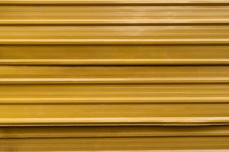 Horizontal corrugated fence of yellow metal sheets. Texture of metal fence picket Profile decking. 写真素材