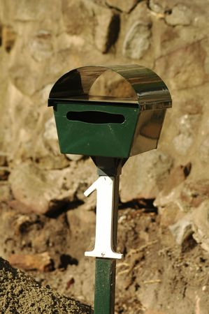 green mailbox with white number one on it, ebhind it is a stone wall photo