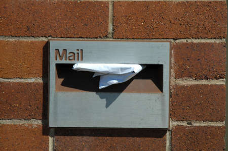 grey maibox in a red brick wall, white paper in it photo
