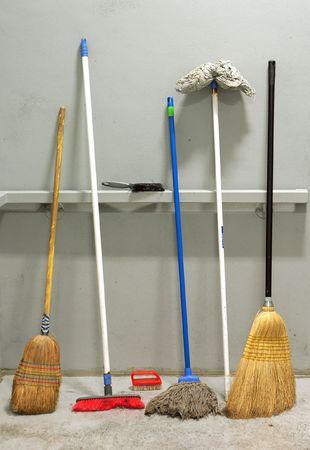d�sinfectant: plusieurs balais utilis�s appuy�e contre mur gris