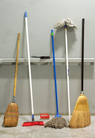 several used brooms leaned against grey wall