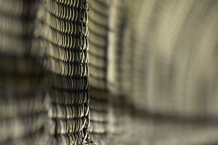 jailhouse: grey wired fence, distance blur, could be a construction site, or a jailhouse