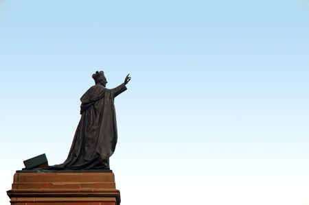hand lifted: dark grey pope sculpture with one hand lifted up, sculpture is on brown stand, light blue sky, Stock Photo