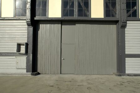 grey door to wooden warehouse, glass windows, footsteps visible on the ground photo