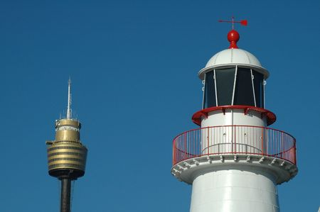 white lighthouse with red parts and sydney tower, blue sky, simple photo photo