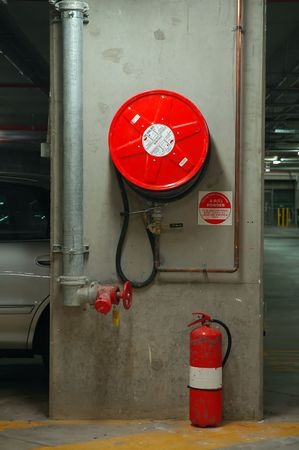 fire hose reel and extinguisher in an underground garage Stock Photo