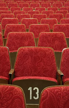 empty red wooden cinematheater seats, number 13 in the middle, Stock Photo