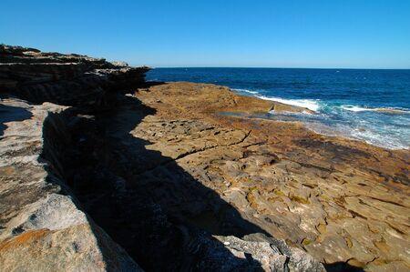rocky coastline, man lying in distance, clear blue sky Stock Photo - 791810