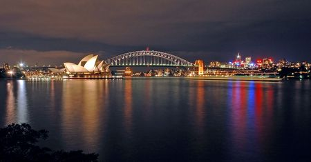 opera house, harbour bridge and north sydney at night; photo taken from royal botanic gardens Фото со стока