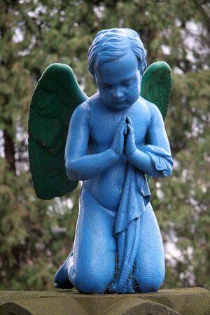 blue praying angel, blurred trees in background, photo taken in Presov, Slovakia Stock Photo - 895574