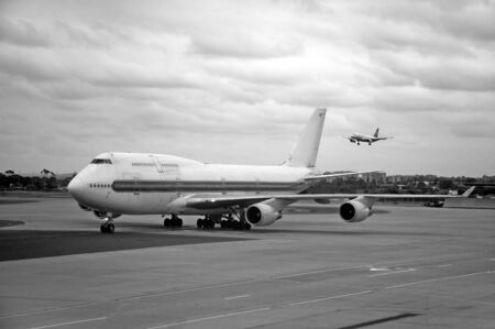 departing: airport scene, rolling plane, landing plane, black and white photo