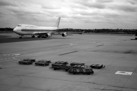 black and white photo of rolling airplane and luggage trolleys Stock Photo - 1118029