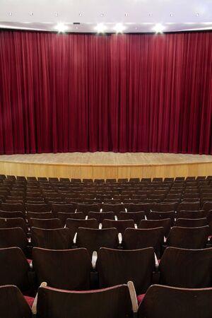 cinema, theater interior; closed red velvet curtain, wooden seats Stock Photo