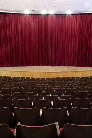 cinema, theater interior; closed red velvet curtain, wooden seats Stock Photo