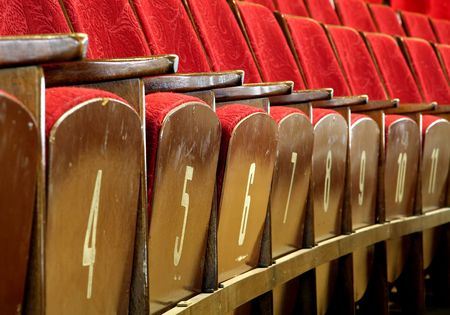 red wooden seats in theatre, numbers on seats