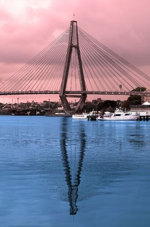 anzac bridge: colored picture of Anzac Bridge in Sydney, blue reflection in water, red sky Editorial
