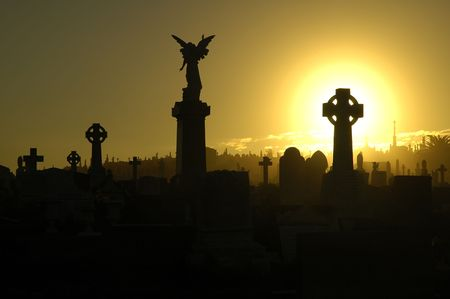 christian crosses: silent evening scene at an old cemetery, silhouettes of graves, crosses and statues, black and yellow dominant colors Stock Photo