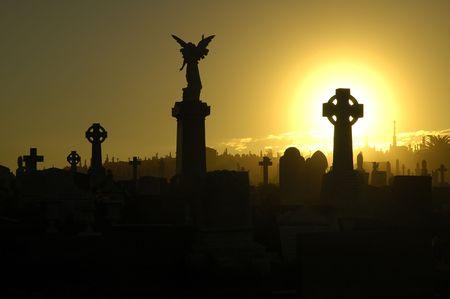 memorial cross: silenziosa sera scena in un vecchio cimitero, sagome di tombe, croci e statue, nero e giallo colori dominanti Archivio Fotografico