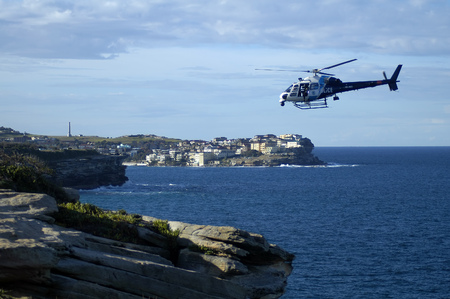 investigators: police helicopter flying above rocky coastline, photo taken in Sydney