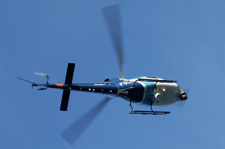 blue and white police helicopter flying above; photo taken in sydney