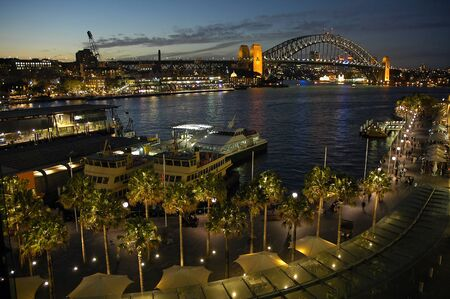 night shot of circular quay in sydney; harbour bridge in background