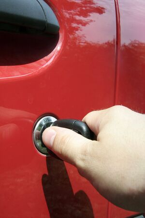 locking up: detail photo of a mans hand locking up a red car Stock Photo