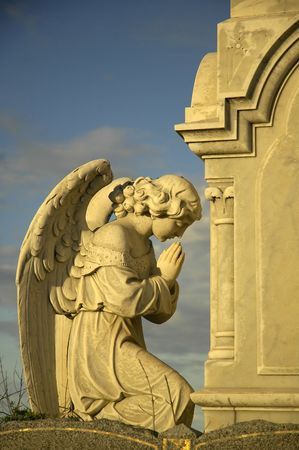angel headstone: angel sculpture praying in front of stone tomb, yellow dusk sun