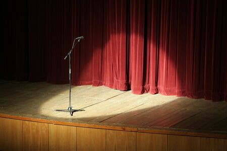 microphone on wooden stage, red curtain in background, spot light