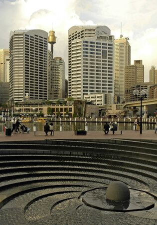 grey photo of Darling Harbour, Sydney Tower in background, modern fountain in foreground photo