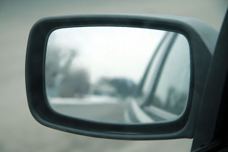 see side: car mirror, mirror in focus, reflection blurred,