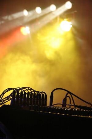 silhouette of music instrument during a concert, lights and fog in background, simple photo