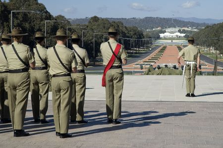 canberra: australian soldiers standing in front of australian war museum in Canberra, modern Parliament House in background, Anzac Parade
