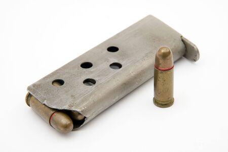 millimetres: ammunition magazine and a single bullet isolated on white background