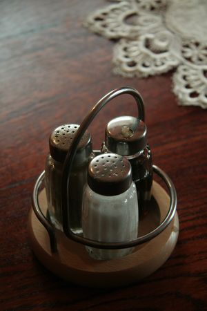 garnishments: oil, salt and pepper in steel basket on wooden table