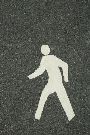 white footpath symbol of walking man, grey asphalt background photo
