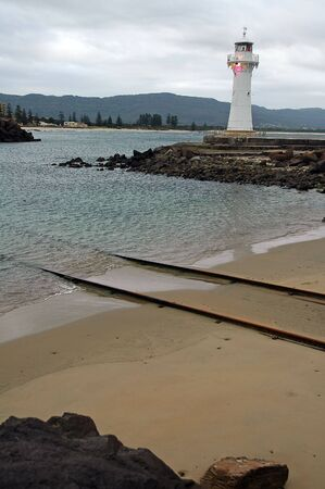 white lighthouse near sydney, rusty train rails leading into water photo