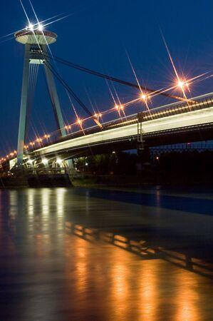 stary: old bridge in bratislava, dusk photo with stary lights, restaurant on top of the bridge Stock Photo