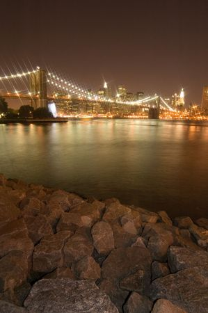 night photo of lighted brooklyn bridge in new york, rocks in foreground photo