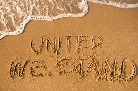 free vote: UNITED WE STAND sign written on a beach, water approaching